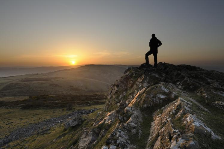 man-standing-mountain-peak-sunset